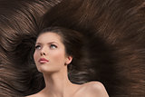 girl with long brown hair looks up