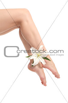 Beautiful woman legs with ankles crossed with a white flower