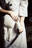 Horror style shot: moppet doll and knife in someone's hands