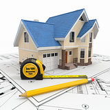 Residential house with tools on architect blueprints.