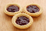 Three tasty jam tarts on a wooden table