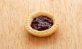 Single tasty jam tart on a wooden table