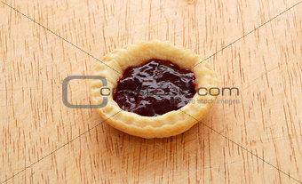 Single tasty jam tart on a wooden table