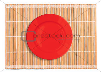 Clear red plate on bamboo placemat isolated on white