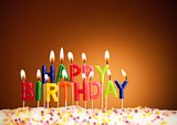 Happy birthday lit candles on brown background