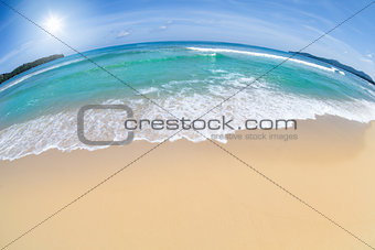wide angle shot of beach with blue sky and sun