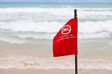 no swimming here dangerous strong current warning flag on beach