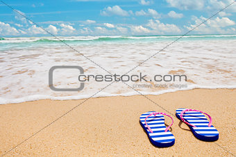 Colorful striped sandals on sea beach