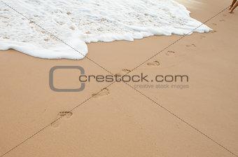 Footprints on sand of ocean beach