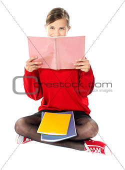 Girl sitting with books on her lap