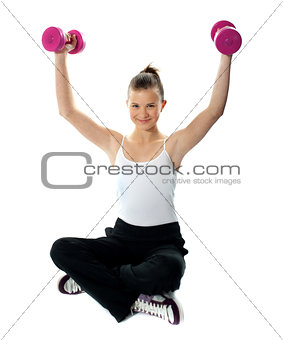 Fit girl with dumbbells in sportswear