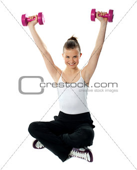 Smiling fit girl working out with dumbbells