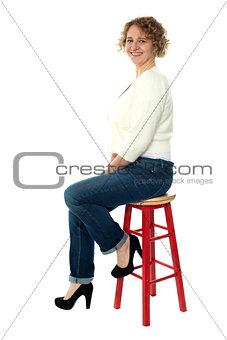 Confident senior woman resting on stool