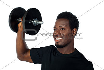 Powerful muscular young man lifting weights