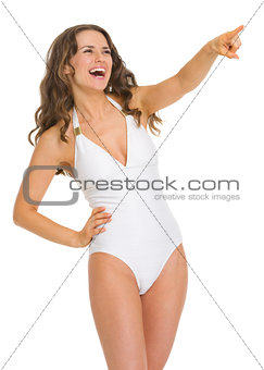 Portrait of young woman in swimsuit pointing on copy space