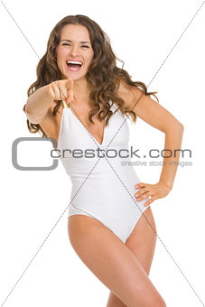 Portrait of young woman in swimsuit pointing in camera