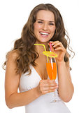 Portrait of happy young woman in swimsuit with cocktail