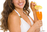 Closeup on smiling young woman in swimsuit with cocktail