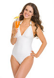 Smiling young woman in swimsuit with cocktail