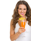 Smiling young woman in swimsuit drinking cocktail