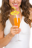 Closeup on young woman in swimsuit drinking cocktail