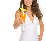 Closeup on young woman in swimsuit giving cocktail