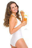 Happy young woman in swimsuit with cocktail