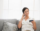 Happy young woman with credit card sitting on sofa and talking m