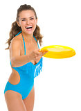 Happy young woman in swimsuit playing with frisbee