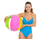 Smiling young woman in swimsuit holding beach ball