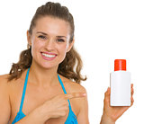 Happy young woman in swimsuit pointing on sun screen creme