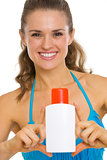 Happy young woman in swimsuit showing sun block creme