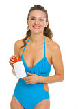 Smiling young woman in swimsuit holding sun screen creme