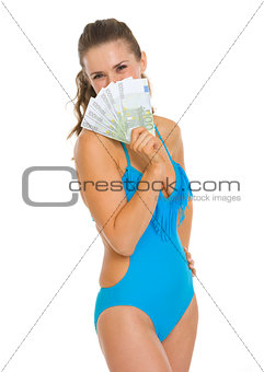Smiling young woman in swimsuit hiding behind fan of euros