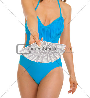 Closeup on fan of dollars in hand of young woman in swimsuit
