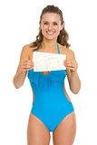 Happy young woman in swimsuit showing air tickets