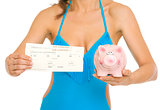 Closeup on young woman in swimsuit showing air tickets and piggy