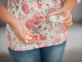 Closeup on pill and glass of water in hand of woman