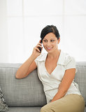 Young woman sitting on sofa and talking mobile phone