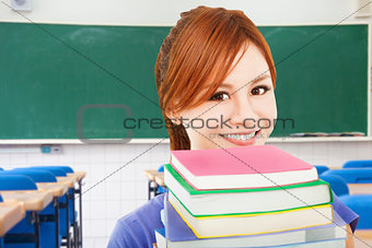 smiling girl holding books in the classroom