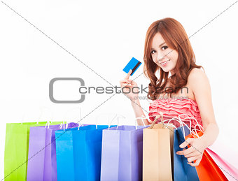 beautiful young woman holding credit card with shopping bags