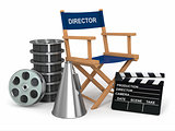 Movie industry. Producer chair, lapperboard and film reelsl.