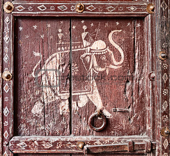 Old wooden door with a picture of an elephant. Fragment.
