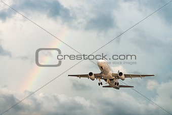 Airplane flying in sky with rainbow