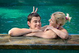Happy playful couple relaxing in a swimming pool