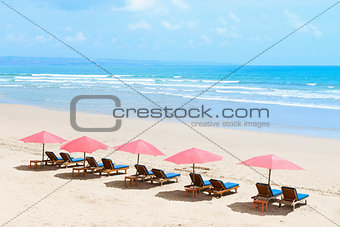 Tropical empty sandy beach with umbrellas