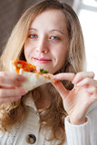 Beautiful young smiling woman eating pizza