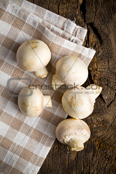 Champignon mushrooms on wooden table.