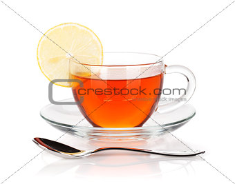 Glass cup of black tea with lemon slice and spoon