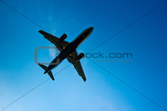 Airliner silhouette against the blue sky